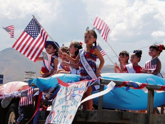 In this file photo, children wave American flags during