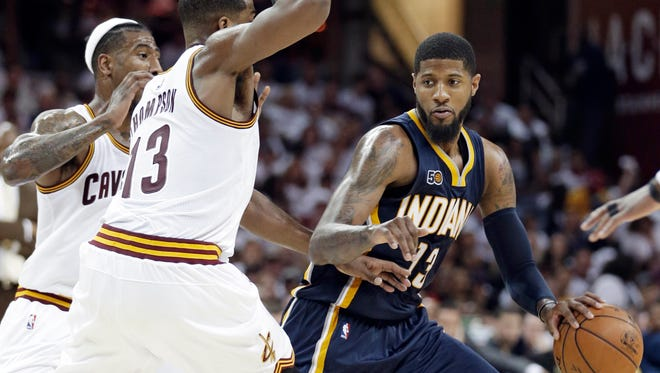 Indiana Pacers' Paul George, right, drives past Cleveland Cavaliers' Iman Shumpert, left, and Tristan Thompson in the second half in Game 2 of a first-round NBA basketball playoff series, Monday in Cleveland.