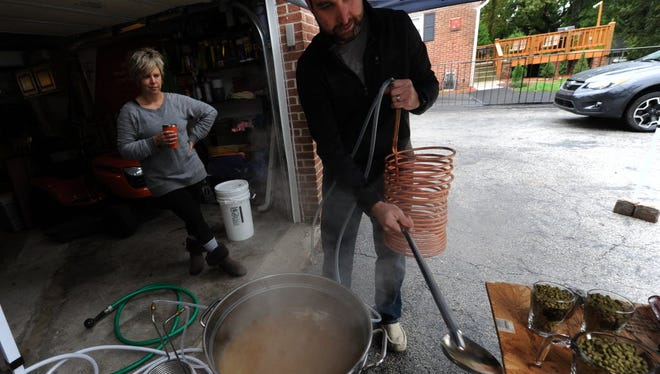 With his wife Brandi looking on, Adam Sauers, the vice president of the York Area Homebrewing Club, places a wort chiller into a brew he is preparing in the back of his Springettsbury home on last month.
