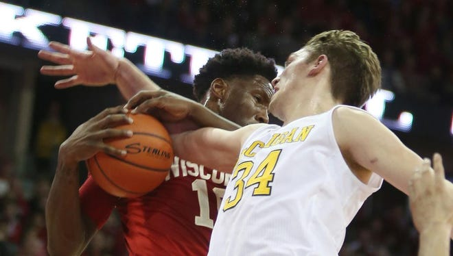Feb 28, 2016; Madison, WI, USA; Wisconsin Badgers forward Nigel Hayes (10) grabs a rebound from Michigan Wolverines forward Mark Donnall (34) during the first half at the Kohl Center.