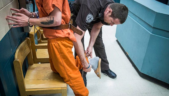 An officer processes an inmate in the intake area of the Delaware County jail.
