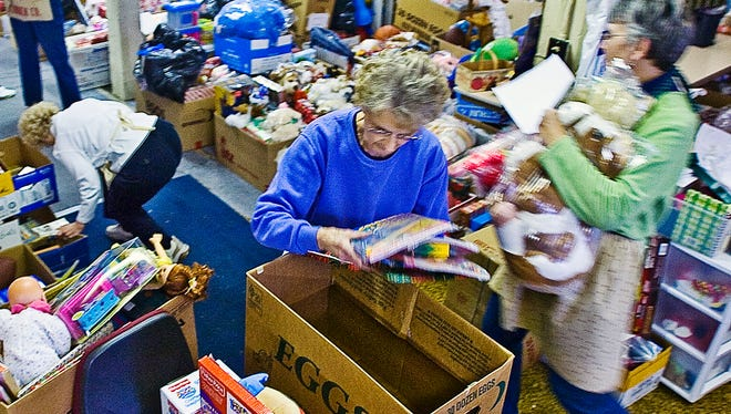 In this 2011 file photo, members of Trinity United Church of Christ along York St. in Hanover pack up Christmas presents for local children at the church's toy shop.