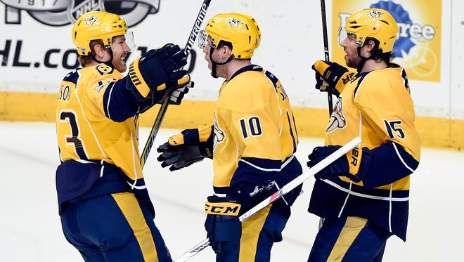 Nashville Predators center Colton Sissons (10) celebrates with left wing Colin Wilson (33) and right wing Craig Smith (15) after Sissons scored a goal against the San Jose Sharks on, March 25, 2017.