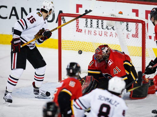 Chicago Blackhawks' Artem Anisimov, left, of Russia, looks on as teammate Nick Schmaltz scores on Calgary Flames goalie Mike Smith during the first period of an NHL hockey game in Calgary, Alberta, Saturday, Feb. 3, 2018. (Jeff McIntosh/The Canadian Press via AP)