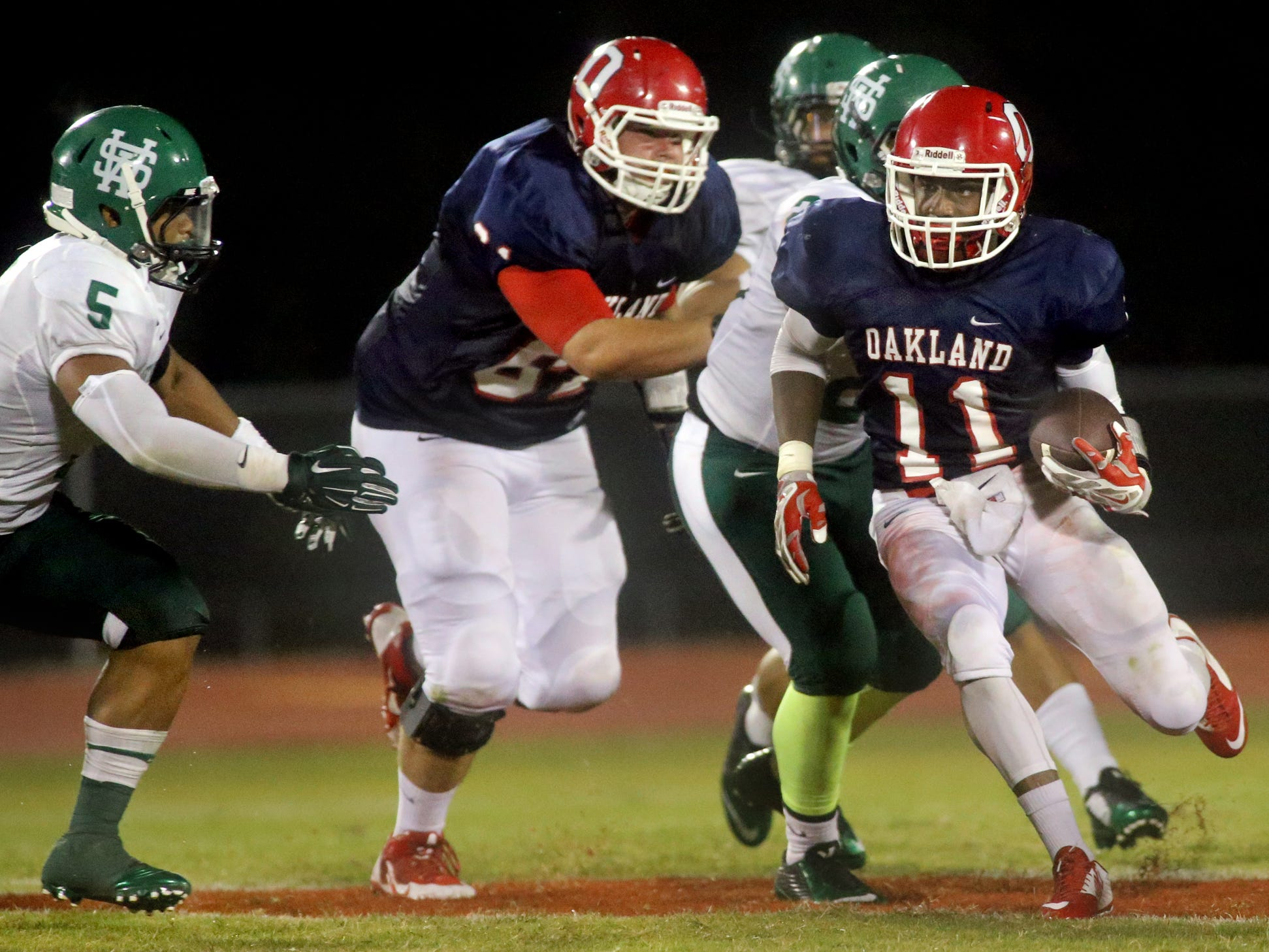 Oakland's Josh Cunningham runs the ball in the first half of the game against White Station at Oakland, on Friday, August 2, 2014.