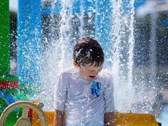 Malachi Bumgardner, 8, keeps cool as he is hit by a wall of water from a water feature at Silver Springs pool on Thursday, June 28, 2018. The Park Board is keeping pools open late as the National Weather Service issued Heat Advisories.