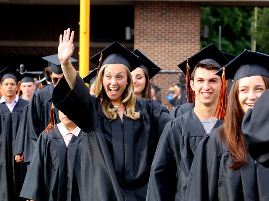 Cassie Budill waves to family as she and classmates