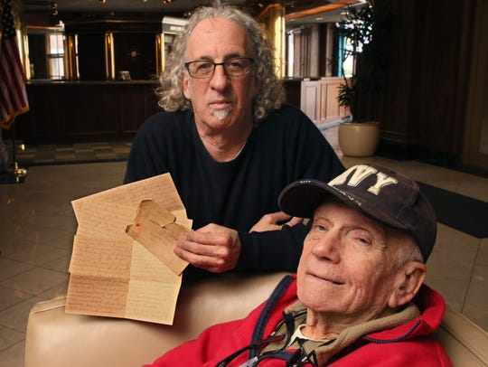 Steve Cohen (rear) holds a letter from his uncle, Albert Cohen, who as a soldier rolled into the Buchenwald death camp in Nazi Germany just days after liberation. Albert Cohen wrote to his mother in Milwaukee and described what he saw there. The letter was found among the possessions of Albert Cohen's brother, Neil Cohen (foreground). It's now in the possession of the United States Holocaust Memorial Museum in Washington, D.C.