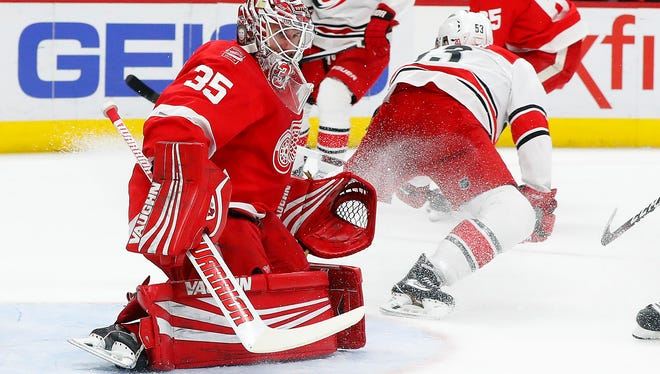 Red Wings goaltender Jimmy Howard (35) deflects a Hurricanes left wing Jeff Skinner (53) shot in the first period on Saturday, Jan. 20, 2018, at Little Caesars Arena.