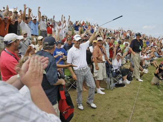 Bryce Molder celebrates with the crowd after his chip from the gallery drops in for birdie Saturday, Aug. 14, 2010, during the third round of the PGA Championship at Whistling Straits.