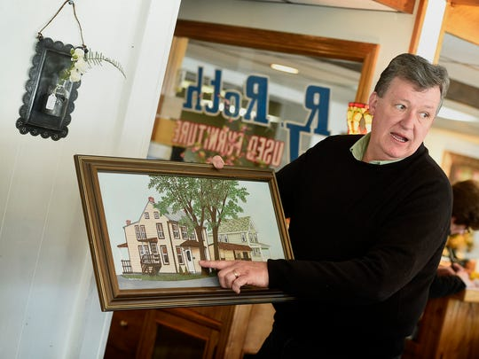 Ron Roth, owner of R.J. Roth Used Furniture at 437 E. Cumberland St., will celebrate 30 years this year. Roth shows off a painting that shows the home that once was his furniture store.