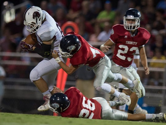 Alabama Christian's Garrett Cottingham (11) is tackled by Trinity's Mays McMillan (48) during the football game at Trinity in Montgomery, Ala., on Friday, Sept. 16, 2016.