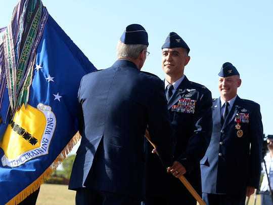 Col. Ricky Mills (center) accepts command of the 17th Training Wing at Goodfellow Air Force Base as Col. Michael Downs looks on during a change of command ceremony Friday, July, 2017.