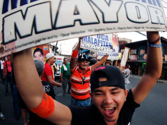 Filipino voters in the street in Calookan city, north of Manila, after the news of a partial count result May 9, 2016.