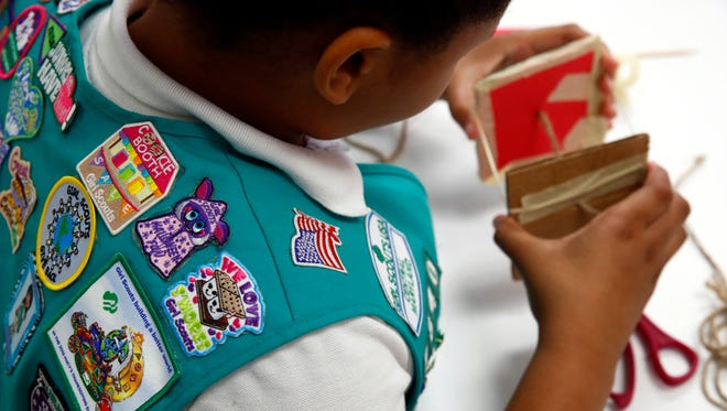 In this July 21, 2017 photo, badges are seen on the vest of a member of the Girl Scouts of Central Maryland as she participates in an activity introducing the world of robotics in Owings Mills, Md. The Girl Scouts of the USA is unveiling a major push this week into furthering the interest of girls in science, engineering, technology and math through 23 new badges, its largest addition of new badges in a decade. (AP Photo/Patrick Semansky)