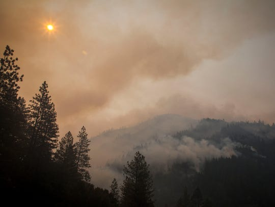 The sun peeks through the smoke and burned out trees