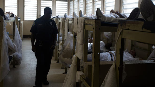Corrections officer J. Spears walks through the sleeping are for inmates coming through intake at Kilby Corrections Facility in Montgomery, Ala., on Friday, Sept. 4, 2015. The facility is currently at 301 percent it's intended capacity. Kilby is currently housing 1,448 inmates and was designed for 440.
