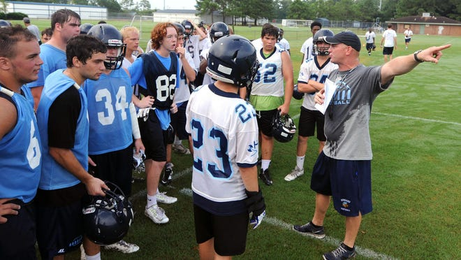 Hoggard head football coach Craig Underwood talks with his team during the first day of practice Saturday morning on the practice fields behind the school in Wilmington.