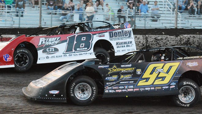 Shannon Babb (18) runs topside while dealing with Frank Heckenast Jr. during late model racing Wednesday at Fairbury Speedway.