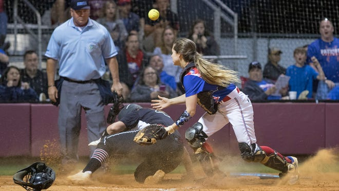 Shelby Ullrich (4) safely slides home as the ball gets away from catcher Autumn Dunlap (21) during the district championship softball between Tate and Pace high schools at Tate High School in Cantonment on Thursday, April 26, 2018.