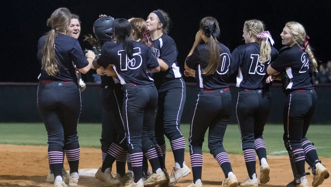 The Aggies celebrate after defeating the Patriots 11-1 during the district championship softball between Tate and Pace high schools at Tate High School on Thursday, April 26, 2018.