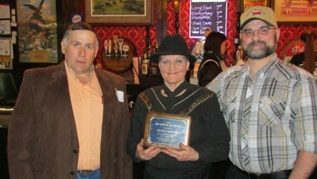 Diane Galbraith Honecker (center) accepts the Iowa Hereford Hall of Fame award for her late father, Lester Galbraith. Also pictured are Bill Goehring, Iowa Hereford Breeders Association president (left); and Mark Honecker, grandson of Lester Galbraith (right).