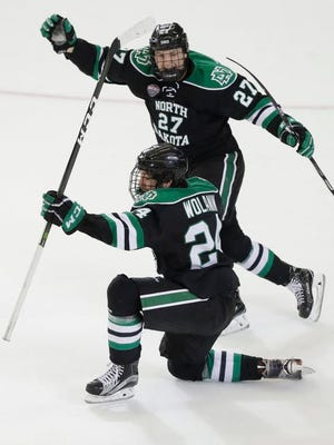 North Dakota defenseman Christian Wolanin (24) celebrates his goal with teammate forward Ludvig Hoff (27) during the third period of an NCAA West Regional college hockey game against Boston University, Friday, March 24, 2017, in Fargo, N.D.