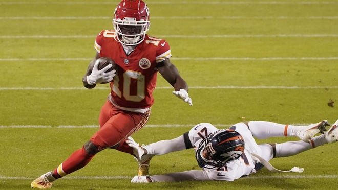 Kansas City wide receiver Tyreek Hill (10) avoids Denver Broncos cornerback A.J. Bouye (21) during Sunday night's AFC West battle. The Chiefs narrowly avoided an upset, pulling out a 22-16 win to clinch a playoff berth.