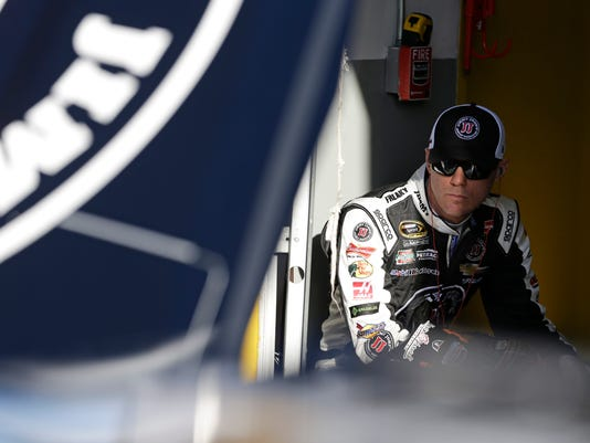 Driver Kevin Harvick waits in his garage before practice for the NASCAR Sprint Cup series auto race at Daytona International Speedway, Friday, Feb. 13, 2015, in Daytona Beach, Fla. (AP Photo/John Raoux)