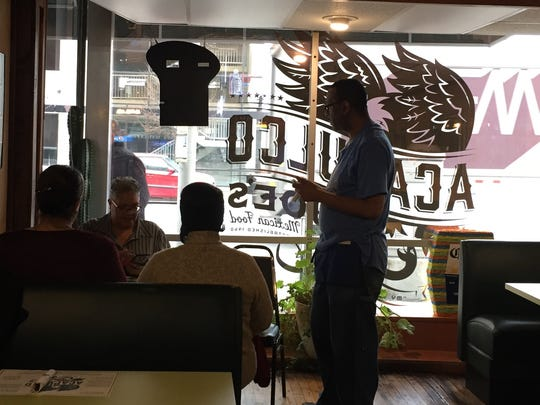 A server takes an order at Acapulco Joe's on Illinois