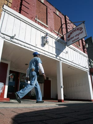 A pedestrian walks by Dimas Montalvo's barbershop on Lower Broadway. The business has been at this location since 1969 and is currently weathering the blight thanks to loyal customers.