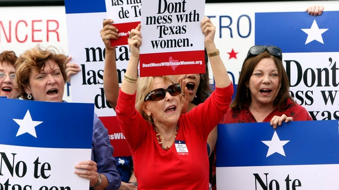 Demonstrators hold up signs March 6, 2012, during Women's Health Express, a bus event held in San Antonio to protest an attempt to cut Planned Parenthood out of the state's Women's Health Plan.