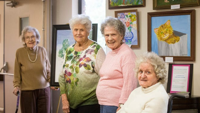 Margaret Skinner, Sara Marcalett, Maxine Byers and Teresa Kennedy stand with their artwork that is for auction at the Golden Living center in Muncie. The residents, who suffer from Alzheimer's are trying to raise money to help Second Harvest Food Bank.