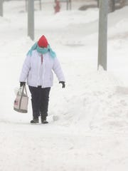 Maureen Garin walks along a snow-covered street in Waukon, Iowa, on Sunday, after a winter storm dumped several inches of snow across the region on Sunday.
