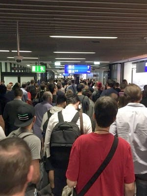 Passengers leave Terminal 1 as they are evacuated at Frankfurt airport on Aug. 31.