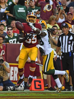 Green Bay Packers cornerback Josh Hawkins (28) breaks up a pass intended for Washington Redskins tight end Vernon Davis (85) during the first half at FedEx Field.