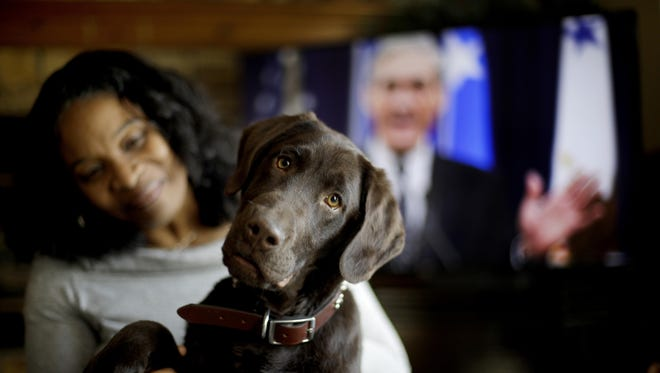 """Alicia Barnett sits with her Chocolate Labrador Retriever named """"Mueller"""" in their Kansas City, Kan., home on March 11, 2019. Barnett named the puppy in honor of special prosecutor Robert Mueller, shown on the television in the background, because the dog seemed strong, quiet, proud and a bit mysterious."""