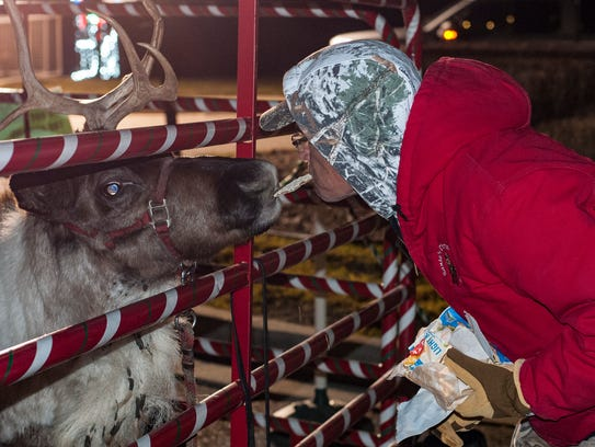 Brian Rezeppa shares a treat with Rudolph the reindeer.