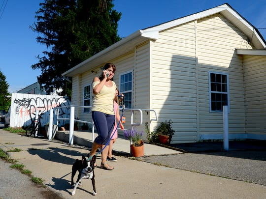 Miss Tickles leads her owners Stephanie Carson and daughter, Elise, 8, past OWL Bakery on Haywood Road on Wednesday, July 20, 2016. After new development along Beacham's Curve the bakery will remain.