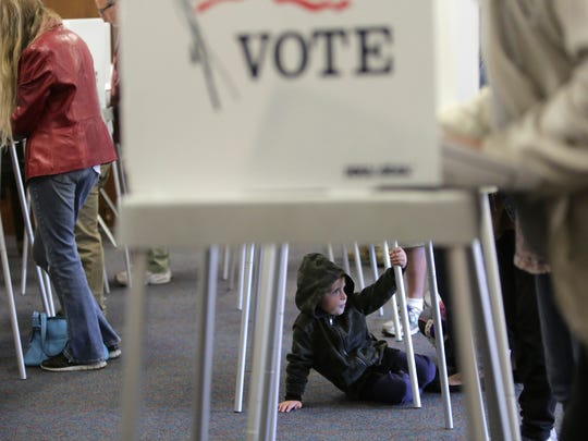 Ephesian Phillips waits for his mother Wanda to finish voting at a polling station in California.