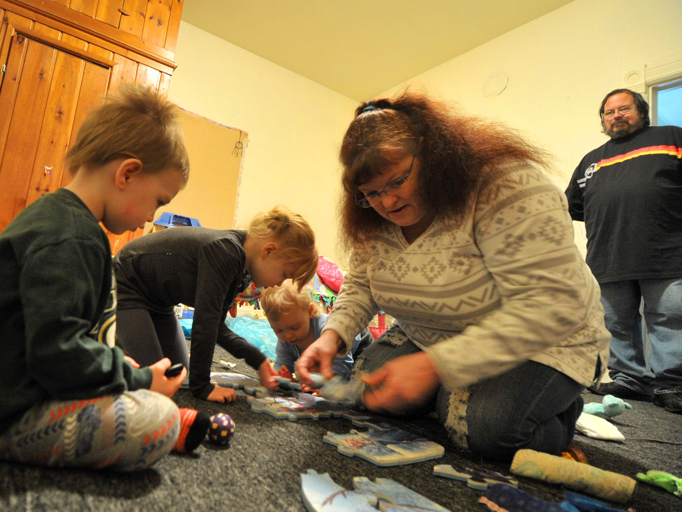 Wanda Worden helps Jaime, Peyton and Jax put together a puzzle in their new home, as Clint Worden looks on.