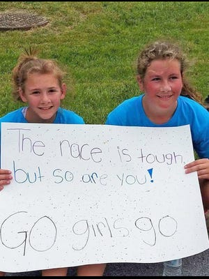 Ella Muldowney, left, and Lilly Garrison hold a sign and cheer on runners at the Go Girls Go 5K on May 20.