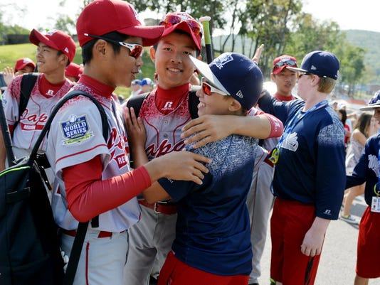 Members of the Tokyo Kitasuna Little League team of Japan and Red Land Little League players, including Bailey Wirt, center, wish each other luck in their games outside Lamade Stadium on Saturday, Aug. 29, 2015, before the Little League World Series U.S. championship game featuring Red Land, Pa., and Pearland, Texas, in South Williamsport.