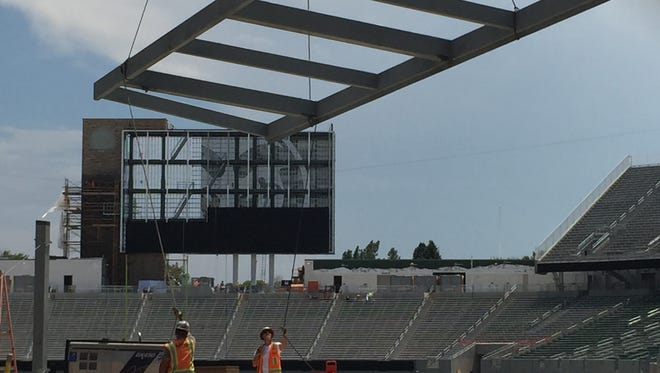 Workers put in place a metal wall with a help of a crane at the New Belgium Porch at the new CSU football stadium Wednesday.