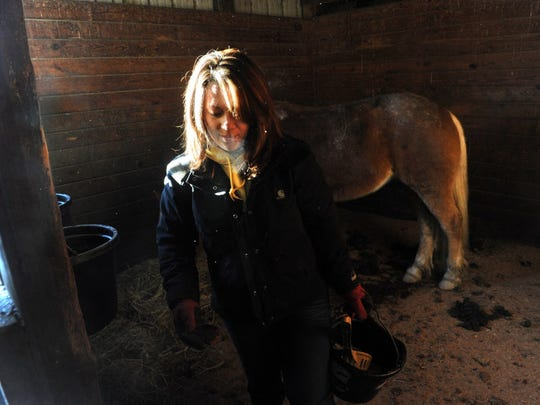 Lacy Delp, daughter of Anne Bathon, cleans out a horse stable in her Codorus Township barn on Friday, Jan. 3, 2014. Bathon was killed Tuesday when she was working on the farm and hay bales fell on her. Lacy, 29, operated the farm with her mom and was the person who discovered her.