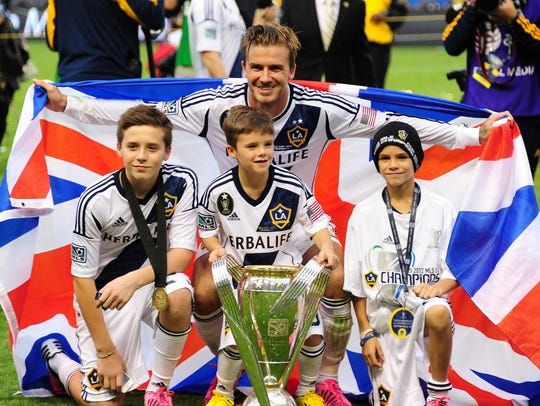 David Beckham poses with his sons Brooklyn, Cruz and