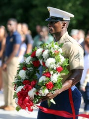 A wreath dedicated to Lance Corporal Brian Montgomery, a US Marine killed while serving in Haditha, Iraq in 2005, is carried by a US Marine during a 9/11 remembrance ceremony held at War Memorial Plaza Sept. 11, 2016.