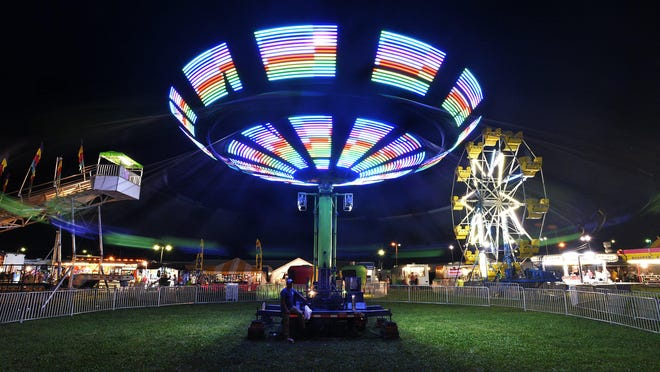 People ride the swings at the Waterford Community Fair in Waterford Township on Sept. 4.