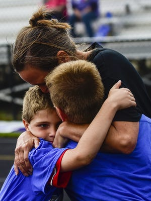 Rosalind Starcher shares an embrace with her grandsons, Calvin and Isaac Mayse, during the 2015 Relay for Life at River Valley High School. She is a survivor of breast cancer.