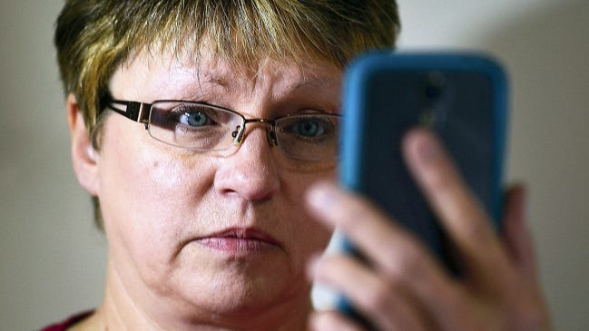 """In this file photo, Vickie Glatfelter holds her cellphone, which has a picture of her son Bob taken after he took a fatal dose of fentanyl. """"When the cops gave me back (his) phone and I flipped it open, that picture was the first thing I saw,"""" she said. She tells her story in a video at yorkdispatch.com. (Randy Flaum - The York Dispatch)"""